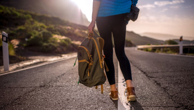 Female hitchhiker walking with backpack on the mountain road. Medium plan rear view without face focused on legs